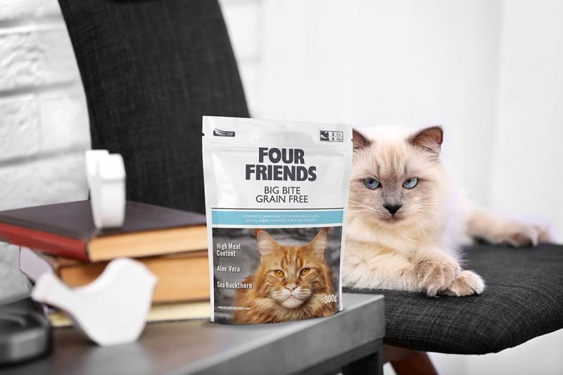 En förpackning kattfoder från Four Friends. I bakgrunden syns en vit katt som ligger på en kontorsstol.